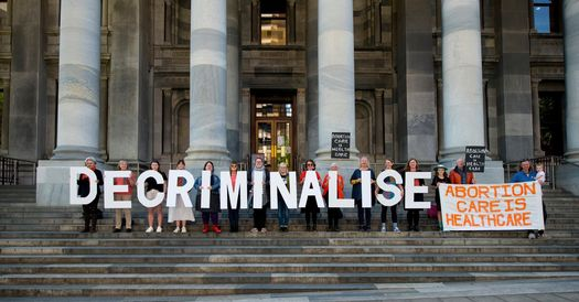 Pro-choice advocates standing on SA Parliament steps holding up signs that spell out 'DECRIMINALISE'